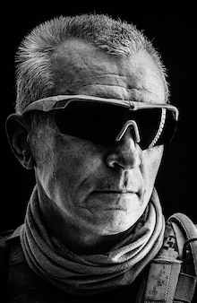 Close up black and white portrait of special forces white-haired veteran in field uniforms, black