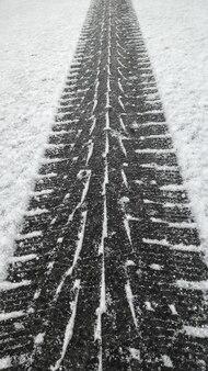 노면의 눈에 검은 겨울 타이어 트레드 발자국을 닫습니다