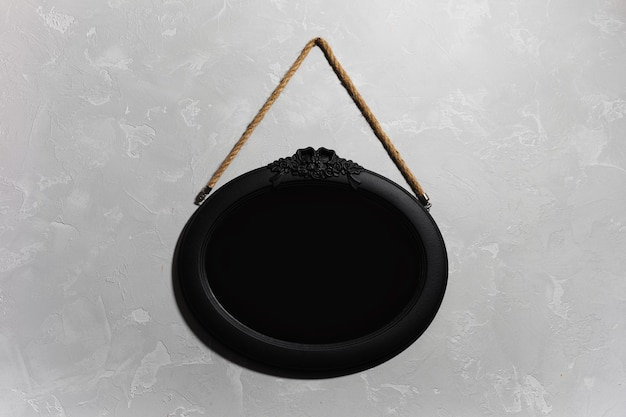 Close-up of black wooden mirror hanging on the grey textured wall.