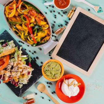 Lavagna del primo piano vicino a pepe e cibo messicano