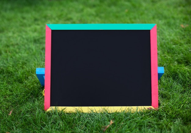 Close-up of blank black schoolboard with colorful frame on green grass