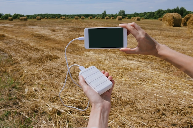 Close up of blank charging the phone from the power bank held in hands