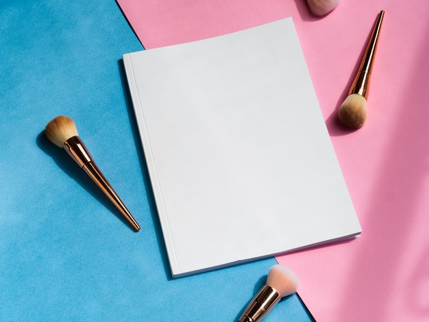 Close-up blank magazine with makeup brushes