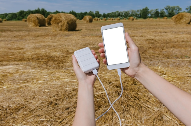 Close up on blank mobile phone with power bank held in hand