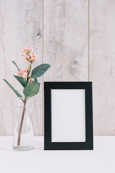Close-up of blank picture frame with flower vase