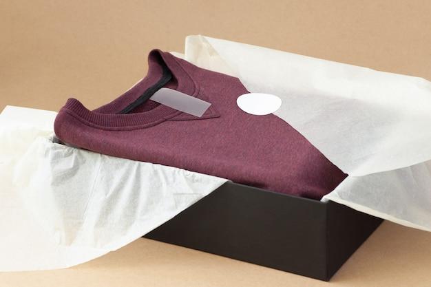 Закройте пустую бирку для инструкций по размеру логотипа на бордовом свитере в черной коробке и белой папиросной бумаге на бежевой крафт-бумаге