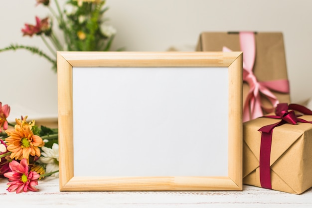 Close-up of blank wooden frame with gift and flowers