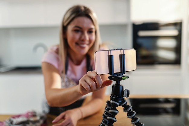 Close-up of blond housewife using smart phone on tripod in a kitchen for searching recipe.