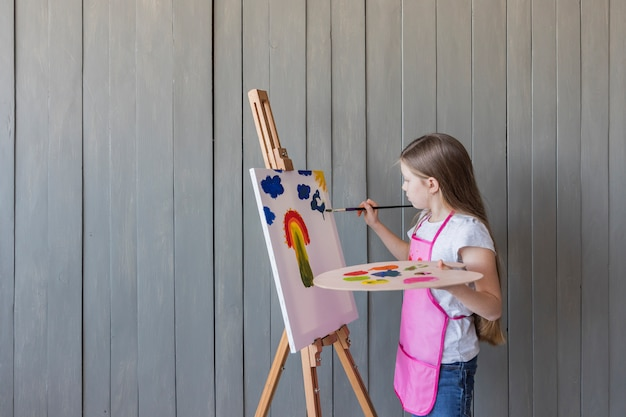 Close-up of a blonde girl painting with paint brush on easel standing against gray wooden wall