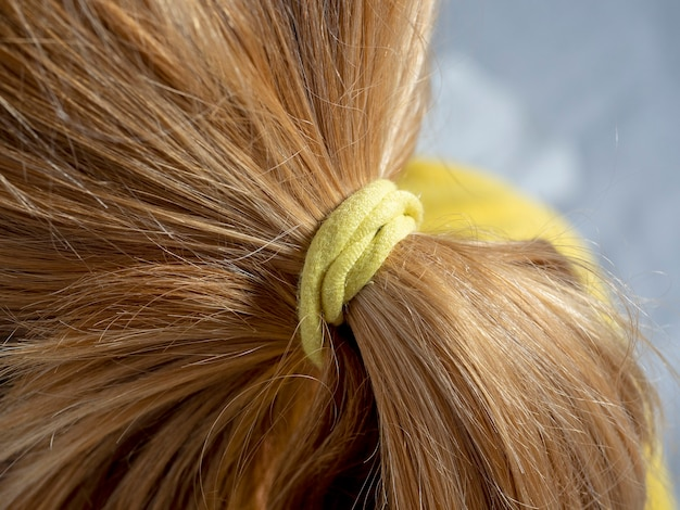Close up of blonde hair tied in a bun with a yellow elastic band