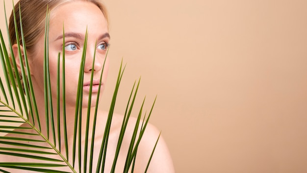 Close-up blonde model behind a plant