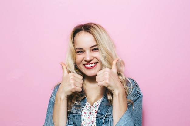 Close-up  of a blonde presents gestures over pink wall