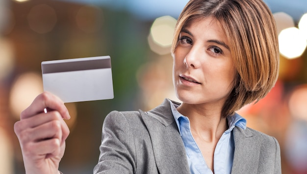 Close-up of blonde woman holding a credit card