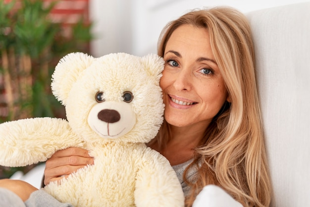 Close-up blonde woman holding teddy bear