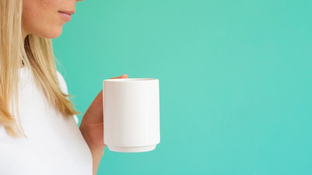Close-up blonde woman holding white mug