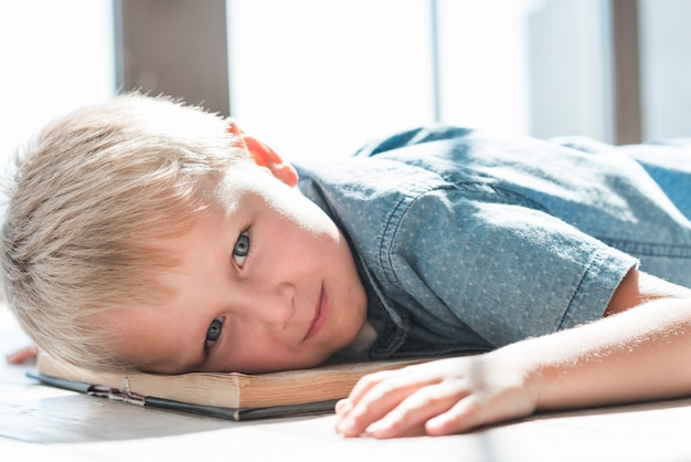 Close-up of blonde young boy leaning head on an open book