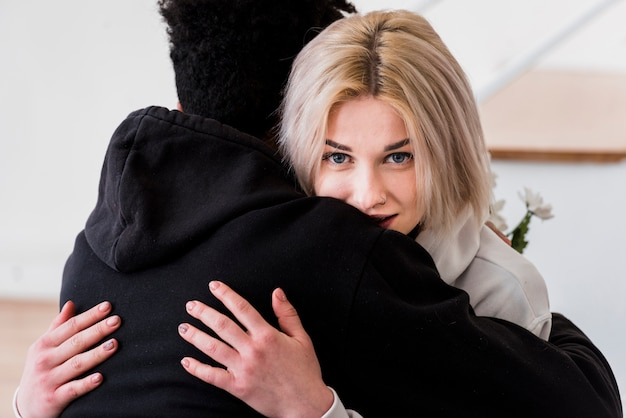 Close-up of blonde young woman embracing her boyfriend