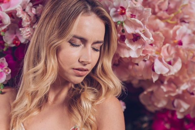 Close-up of blonde young woman with eyes closed standing in front of orchid flowers