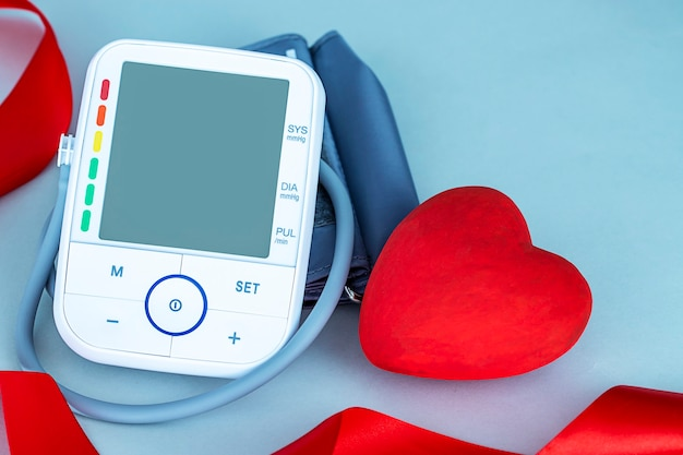 Close up of blood pressure monitor and red heart figure on blue background