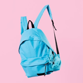 Close-up blue backpack on pink background