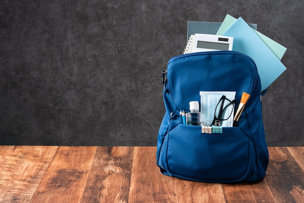 Close up of blue backpack with school stationery over wooden table and black background, back to school design concept.