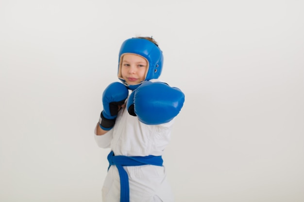 Close-up of a blue boxing glove of a boy boxer in a helmet on a white wall