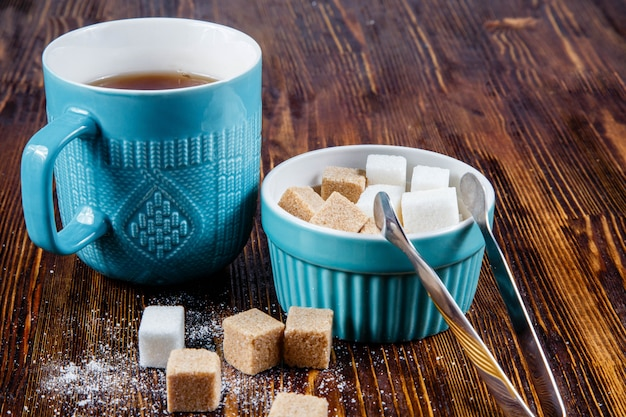 Close-up of a blue ceramic mug with tea and a sugar bowl with cane and white sugar