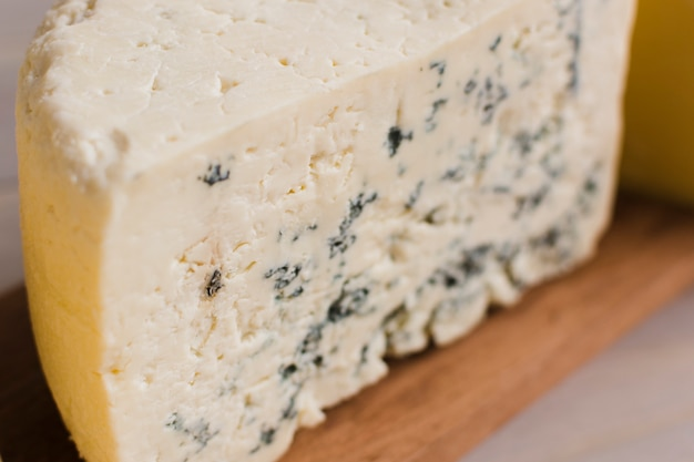 Close-up of blue cheese slice on wooden chopping board