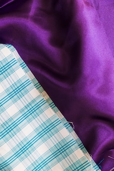 Close-up of blue chequered pattern and plain purple textile