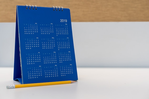 Close up blue color calendar 2019 standing on white table at office