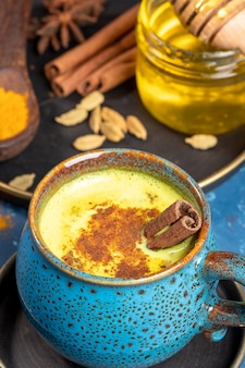 Close-up blue cup of traditional indian ayurvedic golden turmeric milk with ingredients on plate on blue background.