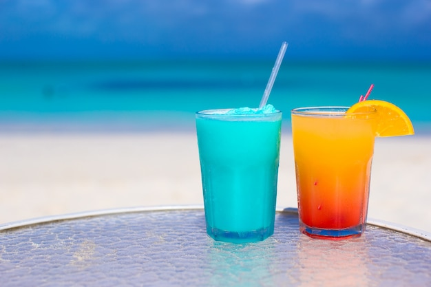 Close up blue curacao and mango cocktail on the white sandy beach