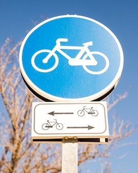 Close-up of blue cycle sign against blue sky