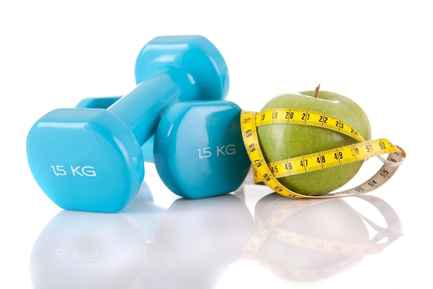 Close up on blue dumbells with apple and measuring tape isolated