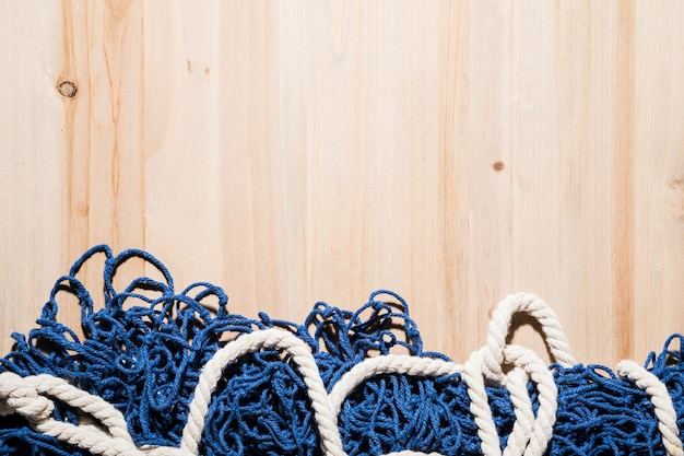 Close-up of blue fishing net with white rope on wooden surface
