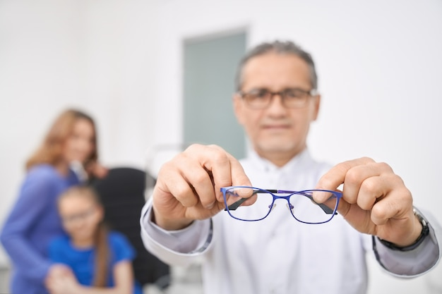 Close up of blue glasses doctor holding in hands.