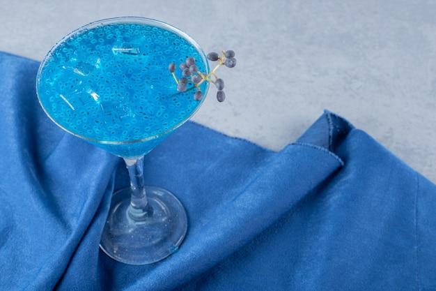 Primo piano di cocktail fatti in casa blu sulla superficie grigia