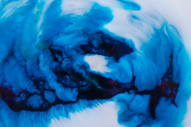 Close-up of blue ink dissolves in white liquid paint