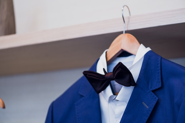 Close-up of blue jacket with bow tie on a hanger.