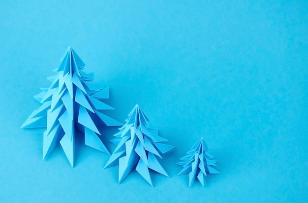 Close up on blue paper origami christmas trees