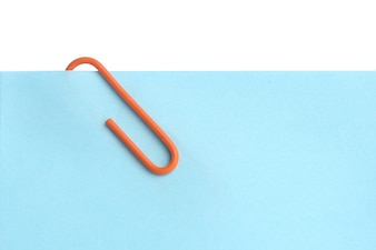 Close up blue post it with orange paper clip on white background
