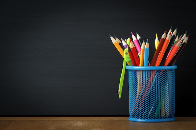 Close-up blue stand with school pencils on the background of a large black chalk board