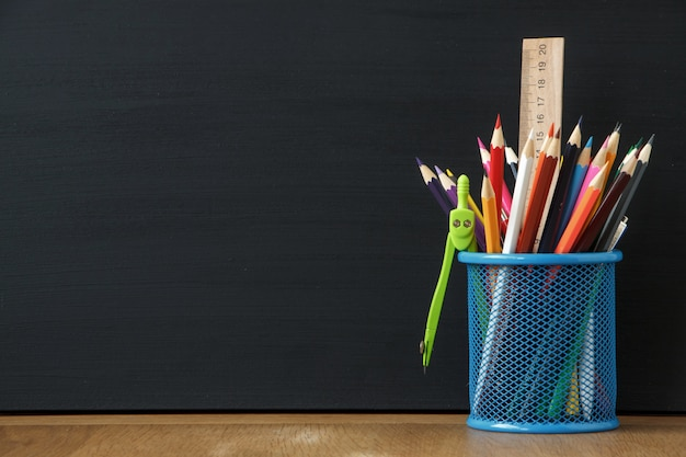 Close-up blue stand with school stationery on the background of a large black chalk board