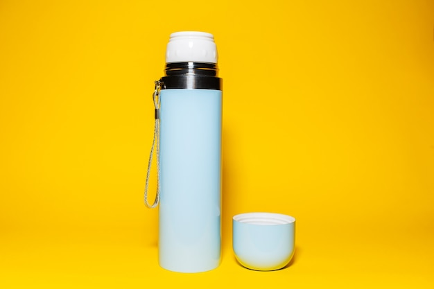 Close-up of blue thermos with cap on yellow b