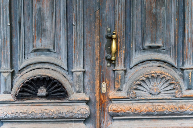 Close up of blue turquoise old textured antique door with gold bronze door handle and keyhole.