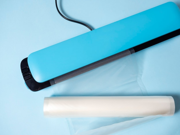 Close-up of a blue vacuum packer on a bright blue background. next to the packaging bags. a machine for preserving the freshness of products.