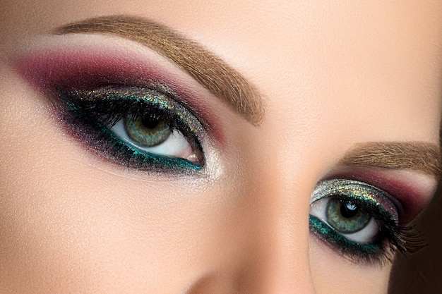 Close up of blue woman eyes with beautiful multicolored smokey eyes makeup