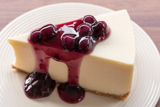 木製のテーブルの上の白い皿にブルーベリークリームチーズケーキを閉じる