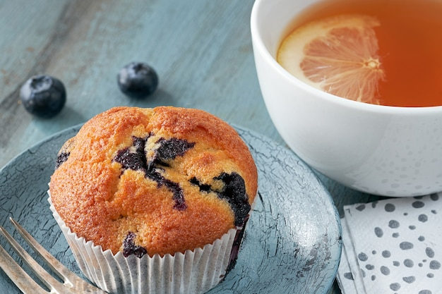 Close-up on blueberry muffin and cup of tea with lemon on gray rustic wood