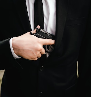 Close up blurred hand with a gun of man in a suit, jacket and white shirt, black tie.
